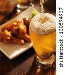 pouring beer with chicken wings in background. - stock photo