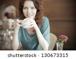 pretty young redhead woman with coffe cup in cafe smile and laugh - stock photo