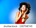 Beautiful smiling woman with afro hair listen to music with headphones on blue background - stock photo