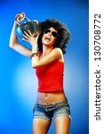 Happy tanned woman with afro haircut enjoying music holding tape recorder. - stock photo