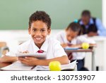primary school boy using tablet compute in classroom - stock photo
