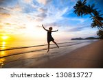 Young girl in a jump on the sea beach at sunset. - stock photo