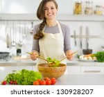 Happy young housewife mixing vegetable salad - stock photo