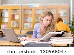 female student with laptop working in library - stock photo