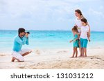 Young man making photo of his wife and kids at tropical beach - stock photo