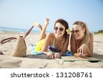 two female friends having fun on the beach - stock photo