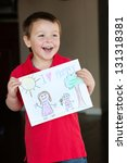 "Happy little boy holding a drawing for his Mom, ""I Love Mommy!"" - stock photo"