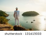 A young man standing on a rock and looking at the sunset of Phuket - stock photo