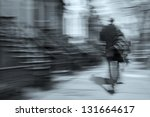 man walking on a city street in motion blur, brownstone buildings as a background, rear view - stock photo