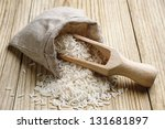 Rice in a sack and spoon on the wooden table - stock photo