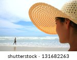 Beautiful woman with big straw hat looking at a man walking on the beach - stock photo