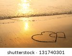 Hearts drawn on the sand of a beach, soft wave of the sea. - stock photo