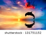 Beautiful calm ocean at sunset. Dolphin jumping silhouette - stock photo