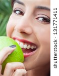 Young woman's face closeup eating a green apple - stock photo
