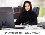 attractive modern Arabian businesswoman in traditional clothing working in office - stock photo