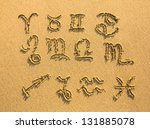 Set of zodiac signs drawn on the facture beach sand. - stock photo