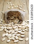 Pumpkin seeds in a sack on the wooden table - stock photo