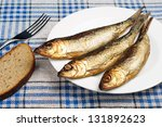 Smoked fish and bread closeup on table - stock photo