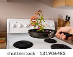chef is tossing veggies into a... | Shutterstock . vector #131906483