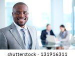 Image of African-American business leader looking at camera in working environment - stock photo