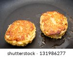 Two Crab Cakes Browning In Hot...