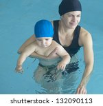 young mother and little son enjoying in a swimming pool - stock photo