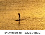 silhouette of man paddleboarding in open water - stock photo