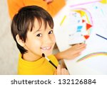 A cute little boy is drawing and being creative with brush - stock photo