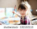 Cute little girl painting a picture in home studio - stock photo