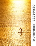 man paddleboarding in open water at sunset - stock photo