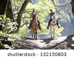 Stock photo horseback riders two attractive women ride horses with backlit leaves behind them 132150803