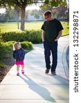 Happy father walking and talking with his adorable toddler daughter - stock photo