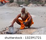 indian sadhu on the send beach of ganges - stock photo