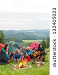 Small photo of Group of friends sitting beside tents, campfire girl playing guitar