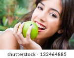 Portrait of a young woman holding a green apple - stock photo