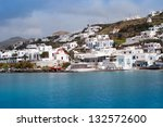 The famous red boat and a church in the bay of Mykonos. - stock photo