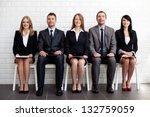 Group of happy business people sitting on chairs - stock photo
