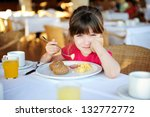 Little sleepy girl eating breakfast in outdoor cafe - stock photo