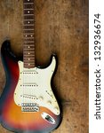 Sunburst color guitar with very old wood surface in background. - stock photo