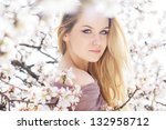 beautiful blonde girl in spring cherry garden - stock photo