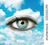 Beautiful blue human eye with bright sky - Spiritual concept - stock photo