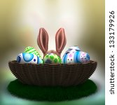 decorated Easter eggs on the grass in basket with Easter Bunny ears - stock photo