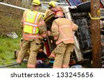 ROSEBURG, OR - MARCH 2013: Emergency workers at the scene of a single car, rollover accident during a spring rain in Roseburg Oregon, March 19, 2013 - stock photo