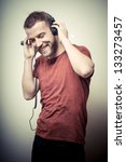 vintage portrait of fashion smiling guy with headphones on gray background - stock photo