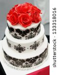 Delicious  black and white wedding cake decorated with sugar red roses - stock photo