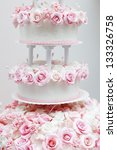 Delicious white wedding cake decorated with pink cream roses - stock photo