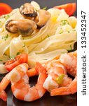 pasta with shrimps, mussels and tomatoes - stock photo