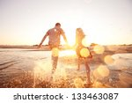 Small photo of happy couple running on the beach