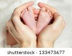 newborn baby   feet in father... | Shutterstock . vector #133473677