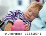 Flying with children. Mother and sleeping two year old baby girl travel on a commercial airliner - stock photo